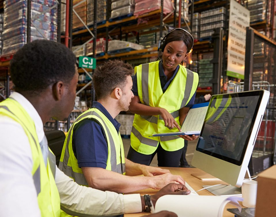 Warehouse workers processing orders through an ERP system.