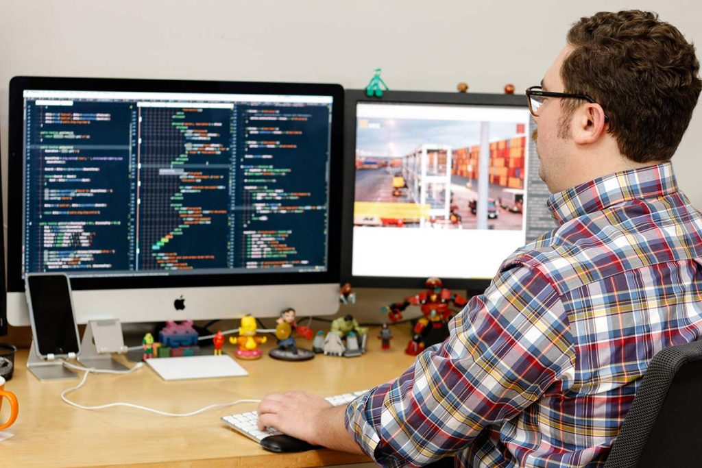A web developer looking at code on multiple monitors