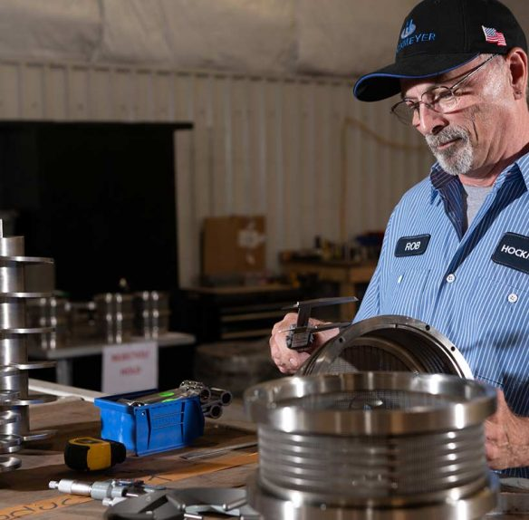 An employee of Hockmeyer Equipment Corporation employee evaluating custom machine parts.