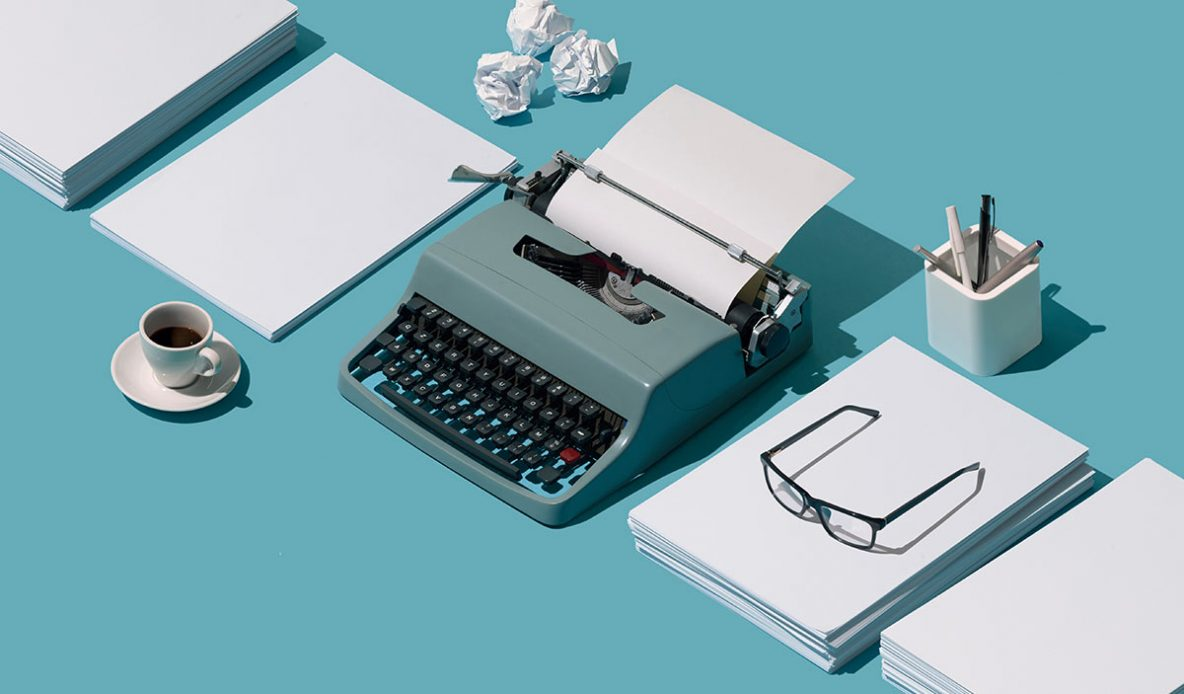 A retro-style typewriter arrainged between stacks of paper