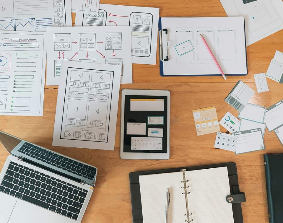 A desk with sketches, a laptop, and printed wireframes for an app