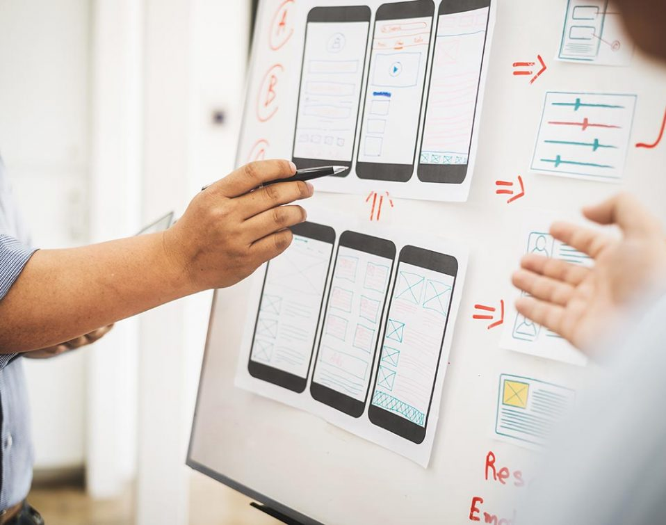 Design professionals planning website layouts on a whiteboard
